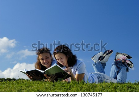 Two happy girls reading books in the nature studying outside in a park lying on green grass - stock photo