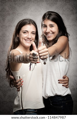 two happy girls showing thumbs up - stock photo