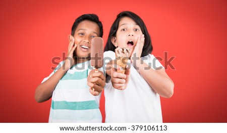 two happy indian kids and ice cream, two asian kids enjoying ice cream or cone or chocolate candy, girl and boy eating ice cream, isolated on red background,  - stock photo