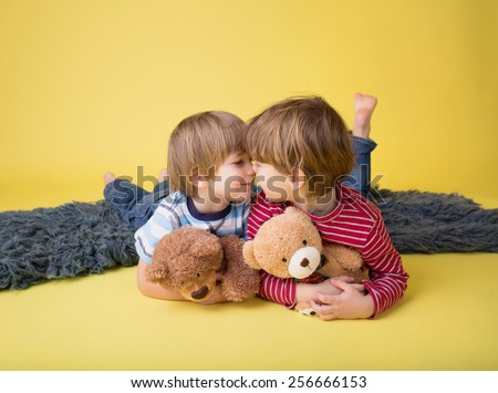 Two happy kids hugging stuffed toy animals, laughing. Siblings, brothers or friends. - stock photo