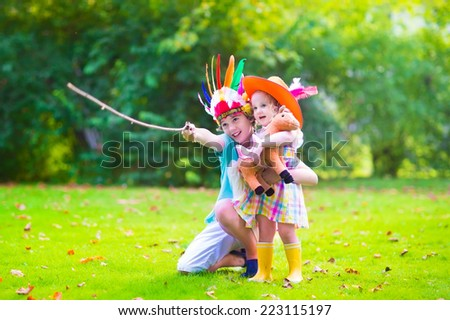 Two happy kids, laughing boy dresed as native American with colorful feather hat and little curly toddler girl in yellow boots with a toy horse playing cowboy outdoors on a sunny summer day - stock photo