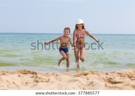 Two happy kids on the beach run out from the sea - stock photo