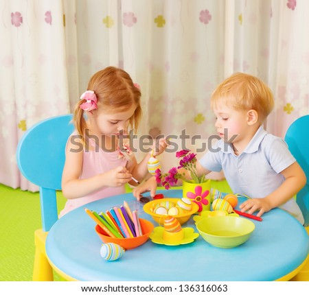 Two happy kids painted Easter eggs at home, traditional christian symbol, celebrating holiday - stock photo