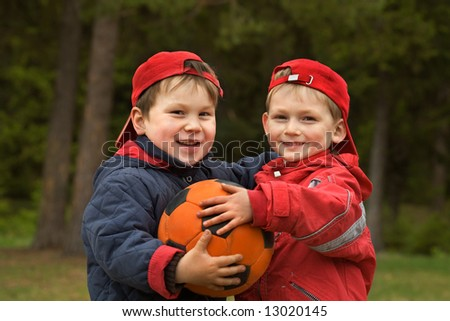 Two happy kids with a ball - stock photo