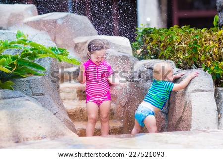 Two happy laughing children, adorable toddler girl and little baby boy, brother and sister, playing together with water tap in a pool on a hot summer day - stock photo