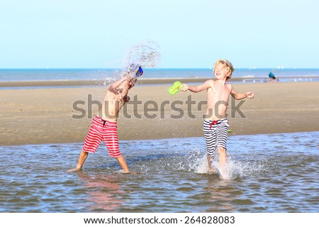 Two happy laughing kids, teenage boys, twin brothers having fun at the North Sea playing together on the beach, running and splashing water from bucket - stock photo
