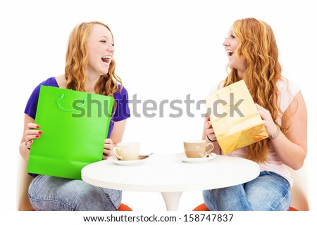 two happy laughing women with shopping bags sitting at a coffee table on white background - stock photo