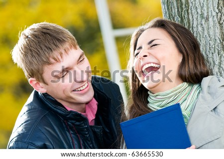 Two Happy laughing young students in autumn outdoors - stock photo