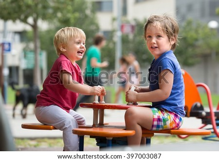 Two happy little  american sisters on teetering board outdoor - stock photo