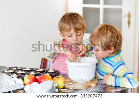 Two happy little blond kid boys baking apple cake in domestic kitchen. Children having fun with working with mixer, eggs and fruits. Tasting dough - stock photo