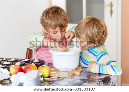 Two happy little blond kid boys, friends baking apple cake in domestic kitchen. Children having fun with working with mixer, eggs and fruits. Tasting dough - stock photo