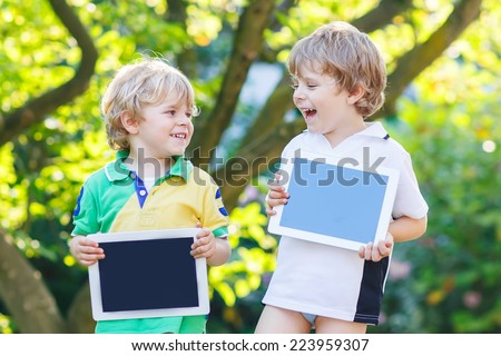 Two happy little boy friends holding tablet pc, outdoors. Kids playing together. - stock photo