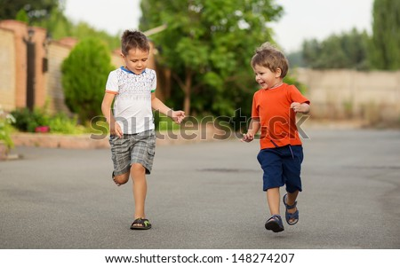 Two happy little boys having fun while running  - stock photo