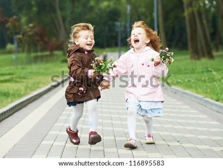 two happy little girls kids having fun while and laughing running in park racing against each other - stock photo