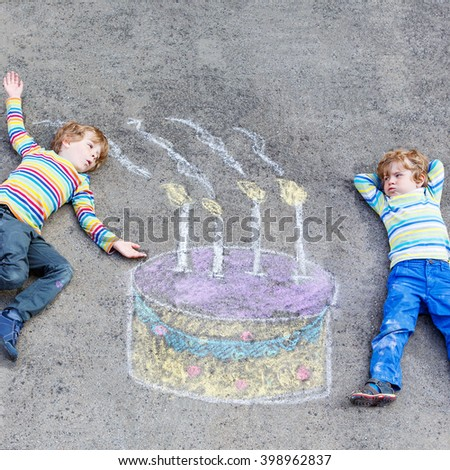 Two happy little kids having fun with big birthday cake picture drawing with colorful chalks. Creative leisure for children outdoors in summer. Kids blowing candles. - stock photo