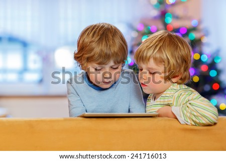 Two happy little kids playing with tablet pc, indoors. Sibling toddlers looking at tablet. With Christmas tree and lights on background. - stock photo