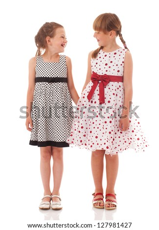 Two happy little sisters walkinjg isolated on white - stock photo