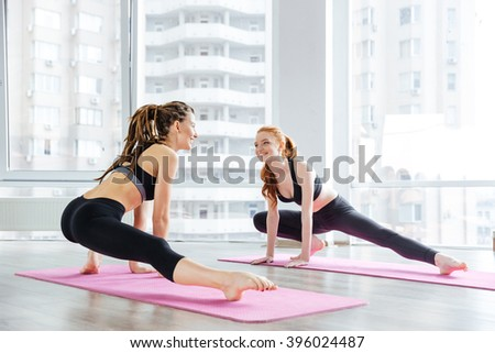 Two happy lovely young women doing stretching exercises together in yoga studio - stock photo