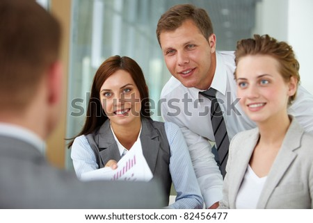 Two happy managers looking at business partner at meeting - stock photo