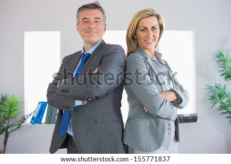 Two happy mature businesspeople looking at camera standing firmly back to back with crossed arms at office - stock photo