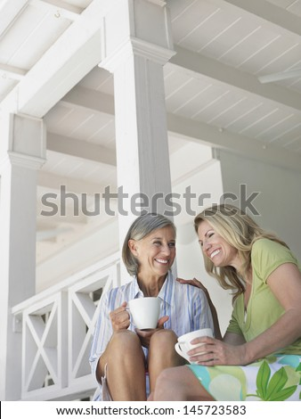 Two happy middle aged women sitting on verandah with coffee cups - stock photo