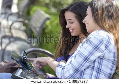 Two Happy Mixed Race Students Using Touch Pad Computer Outside Together on Campus. - stock photo