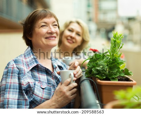 Two  happy pensioner drinking coffee on balcony and smiling - stock photo