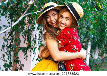 Two happy pretty young sisters, hugs smiling laughing  and having funny crazy time together, bearing stylish retro vintage feminine clothes and hats. Outdoors. - stock photo
