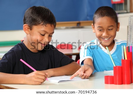 Two happy school boys sharing learning in class - stock photo