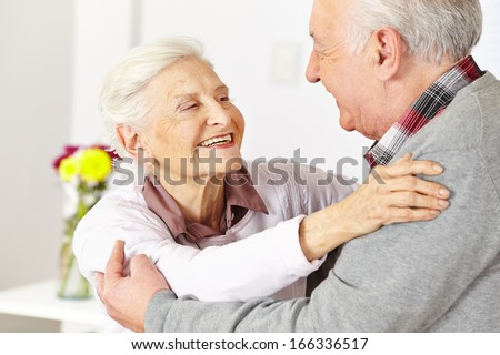 Two happy senior citizens dancing and smiling in a dancing class - stock photo