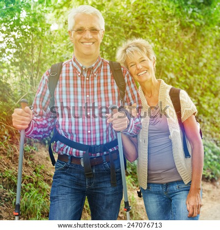 Two happy senior people hiking in summer in nature - stock photo