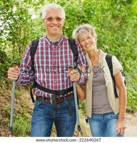 Two happy senior people hiking together in nature in summer - stock photo