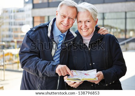 Two happy seniors on city trip with map - stock photo