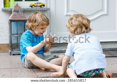 Two happy sibling boys having fun and playing together in summer garden, outdoors. On warm sunny day. Selective focus on one child. - stock photo