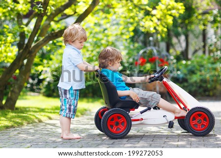 Two happy sibling boys playing together with toy car in summer garden, outdoors. - stock photo
