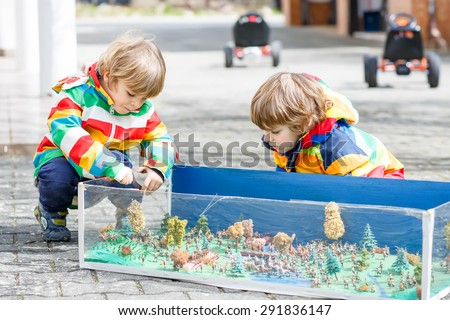 Two happy sibling boys playing with soldiers toys. Active leisure with kids outdoors  on warm spring or autumn day. - stock photo