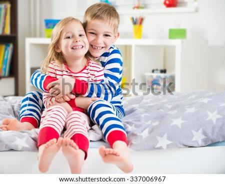 Two happy siblings in striped sleepwears in bed - stock photo