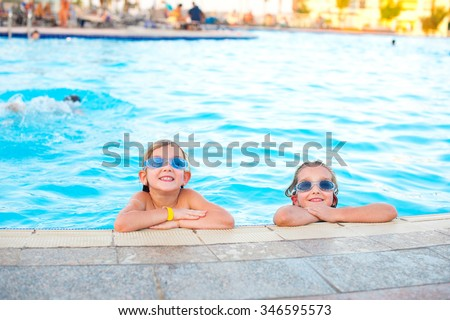 Two happy sister girl in swim glasses play in blue water of pool in tropical resort - stock photo