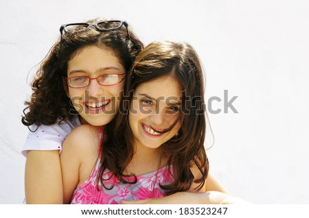 Two happy sister girls hugging and laughing against a white wall - stock photo