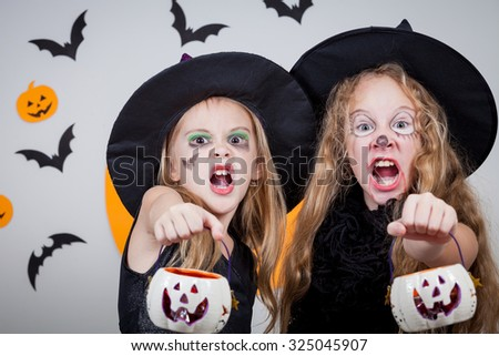Two happy sisters on Halloween party - stock photo