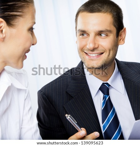 Two happy smiling businesspeople or client and business man, giving pen for signing document - stock photo