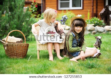 Two happy smiling girls having picnic on a green lawn in front of country house - stock photo