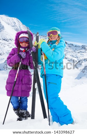 Two happy smiling girls with cross country ski standing together at winter - stock photo