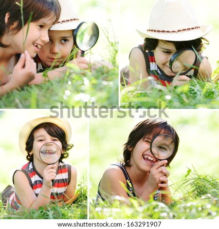 Two happy smiling kids exploring nature with magnifying glass - stock photo