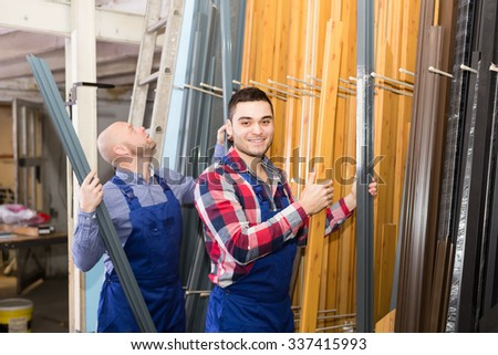 Two happy smiling workmen in uniform choosing PVC window profile at stand - stock photo