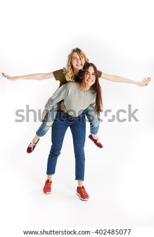 Two happy smiling young pretty girls in jeans, funny girl jumps on girl back. White background - stock photo