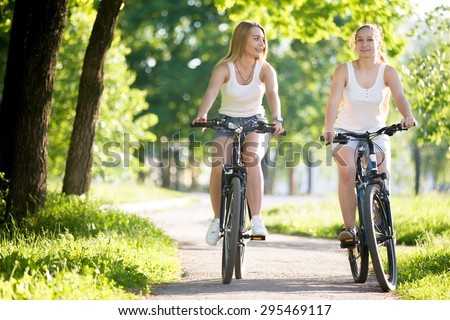 Two happy smiling young women girlfriends wearing jeans shorts enjoy riding bicycles on street on sunny summer day, having conversation - stock photo