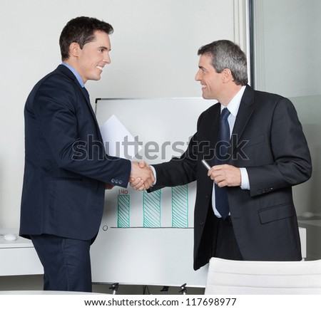 Two happy successful business partner shaking hands in the office - stock photo