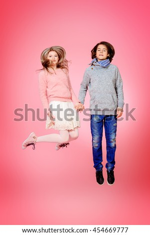 Two happy teenage boy and girl jumping together over pink background. Friendship. First love. - stock photo