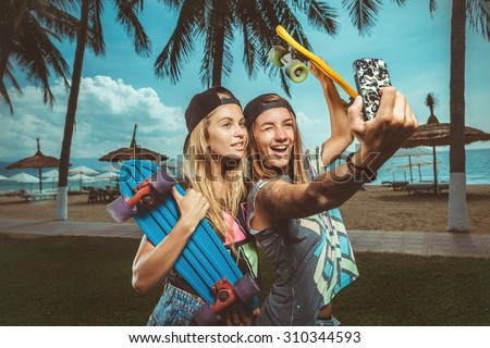 Two happy teenage girlfriends taking a selfie with smartphone outdoors on sunny summer day - stock photo
